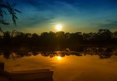 Crepúsculo sobre el lago y un barco cerca de la costa Foto de archivo libre de regalías