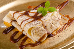 Crepe with banana slices and sauce Stock Images