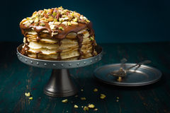 Crepe cake with chocolate and nuts. Crepe cake with custard cream and chocolate topping and nuts royalty free stock images