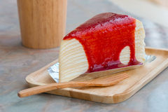 Crepe cake with strawberry sauce in wooden tray Royalty Free Stock Photography