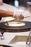 Crepe Chef. In the process of making a crepe using commercial grade cooking equipment stock photos