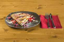 Crepe with chocolate cream, chocolate chips, banana and strawberry served on grey plate Stock Photos