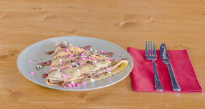 Crepe with chocolate cream and chocolate chips served on white plate Royalty Free Stock Images