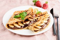 Crepe with chocolate spread and banana on white plate. On pink background. Tasty dessert stock photography