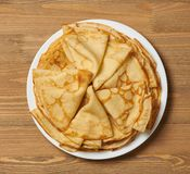 Crepe closeup, heap of thin pancakes on a dish, wood background stock images