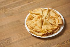 Crepe closeup, heap of thin pancakes on a dish, wood background stock photo