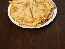 Crepe closeup, heap of thin pancakes on a dish, wood background stock photos