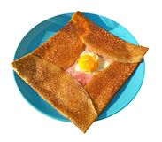 Crepe complet on blue plate on white background - traditional breton meal: pancake from buckwheat flour with. Ham, cheese and egg inside stock images