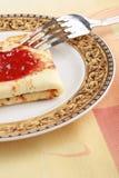 Crepe deliciosa con el atasco rojo en una placa Foto de archivo libre de regalías