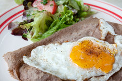 Crepe with egg. French pancake savoury with egg and salad garnish Royalty Free Stock Image