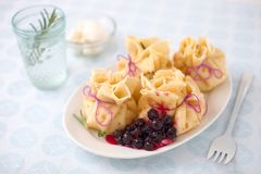 Crepe purse. Filled with black currant on a white plate royalty free stock images