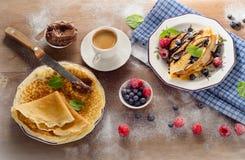 Crepes με τα φρέσκα μούρα, την κρέμα σοκολάτας και το φλιτζάνι του καφέ για Στοκ εικόνα με δικαίωμα ελεύθερης χρήσης
