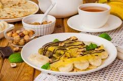 Crepes или блинчики с сливк шоколада, бананами и фундуками для завтрака Стоковые Фотографии RF