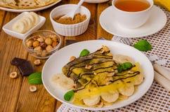 Crepes или блинчики с сливк шоколада, бананами и фундуками для завтрака Стоковое Изображение
