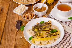 Crepes или блинчики с сливк шоколада, бананами и фундуками для завтрака Стоковое Изображение RF