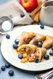 Crepes with apple filling, blueberry and caramel sauce. Homemade pancakes in the form of triangles with apple filling, blueberry and caramel sauce on a plate stock image