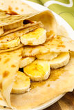 Crepes with banana, maple syrup and sugar powder. Crepes or pancakes with banana, maple syrup and sugar powder Royalty Free Stock Photos