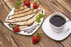 Crepes with Banana and strawberries. Crepes with Banana, Chocolate and strawberries on a wooden background, pancakes Stock Image
