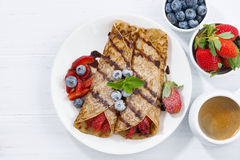 Crepes with berries and chocolate sauce for breakfast, top view Stock Photo