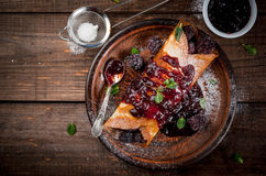 Crepes with berry and jam. Delicious homemade breakfast: french crepes with forest fruit, topped with jam and filled with forest fruit, sugar and mint, top view Royalty Free Stock Photo