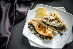 Crepes with black caviar Stock Images