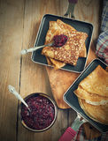 Crepes with black currant jam Royalty Free Stock Photos