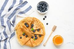 Crepes or blini with fresh berries and honey. On white background. Table top view with copy space stock photo