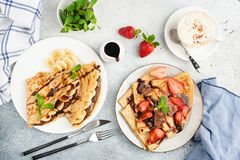 Crepes or blini with fruits, cup of coffee. Crepes or blini with banana, strawberry and chocolate, cup of coffee and decoration of mint leaf and chocolate sauce stock photography