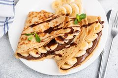 Crepes or blini stuffed with chocolate, banana. Crepes or blini stuffed with chocolate hazelnut spread, banana on a white plate. Closeup view stock images
