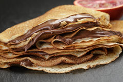 Crepes or blinis with chocolate cream and orange Stock Images
