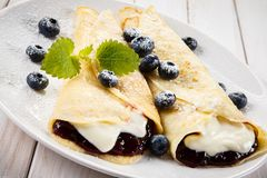 Crepes with blueberries and cream on wooden background Stock Photos
