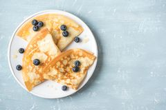 Crepes with blueberries and honey. Homemade pancakes, crepes on blue table, copy space stock photo
