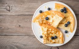 Crepes with blueberries and honey. Homemade pancakes, crepes on wooden table, copy space royalty free stock image