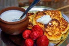 Crepes/bu?uelos del syrniki del reques?n/de la cuajada con las fresas y la crema frescas Desayuno ucraniano y ruso tradicional fotografía de archivo libre de regalías