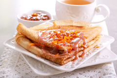 Crepes with caramel sauce. Cup of tea stock photography