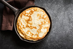 Crepes in cast iron pan. Homemade crepes in cast iron pan over rustic black background with copy space - cooking fresh homemade breakfast crepes pancakes food Stock Photos
