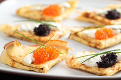 Crepes with caviar. Crepes with red and black caviar on a plate Royalty Free Stock Photo