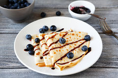 Crepes with chocolate sauce and berries Stock Photos