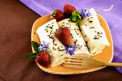 Crepes Chocolate Strawberries. Crepes On Golden Plate With Mint, Chocolate Sprinkles, Strawberries And Edible Borage Flowers Royalty Free Stock Photos