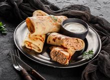 Crepes with chopped meat, greens and sour cream on black plate over dark background. Pancake week or Shrovetide. Healthy breakfast. Top view, flat lay stock photography