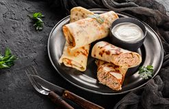 Crepes with chopped meat, greens and sour cream on black plate over dark background. Pancake week or Shrovetide. Healthy breakfast. Top view, flat lay royalty free stock photo