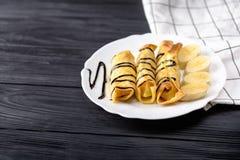 Crepes con el jarabe de chocolate del plátano en fondo de madera negro Visión superior con el espacio de la copia Imagen de archivo