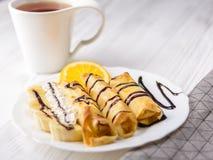 Crepes con el plátano, crema azotada adornada con el jarabe de chocolate en el fondo de madera blanco Y una taza de té Imagenes de archivo