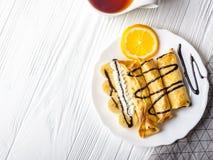 Crepes con el plátano, crema azotada adornada con el jarabe de chocolate en el fondo de madera blanco Y una taza de té Imágenes de archivo libres de regalías