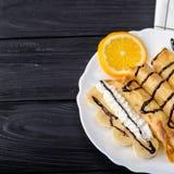 Crepes con el plátano, crema azotada adornada con el jarabe de chocolate en fondo de madera negro Visión superior con el espacio  Imagen de archivo