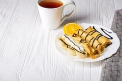 Crepes con el plátano, la crema azotada adornada con el jarabe de chocolate en el fondo de madera blanco y la taza de té Imágenes de archivo libres de regalías