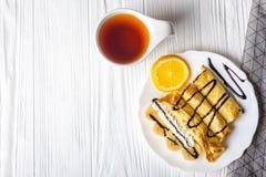 Crepes con el plátano, la crema azotada adornada con el jarabe de chocolate en el fondo de madera blanco y la taza de té Imagen de archivo
