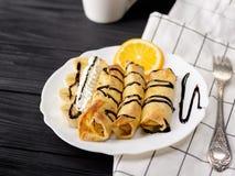 Crepes con el plátano, la crema azotada adornada con el jarabe de chocolate en fondo de madera negro y la taza Imagen de archivo