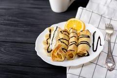 Crepes con el plátano, la crema azotada adornada con el jarabe de chocolate en fondo de madera negro y la taza Fotos de archivo libres de regalías