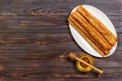 Crepes con la miel en un fondo de madera Imagen de archivo